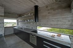 12 Inspirational Examples Of Letterbox Windows In Kitchens // This skinny letterbox window brightens up the dark black cabinets and concrete used throughout this kitchen, and looks out over the nearby golf course.
