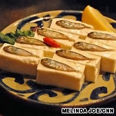 Sukugarasu, firm tofu topped with salted baby fish, is a classic Okinawan accompaniment to sake or awamori.  Each piece should be eaten in one bite. The intense briny flavor of the fish complements the mildness of the tofu.  Okinawan cuisine: The Japanese food you don't know   CNN Travel