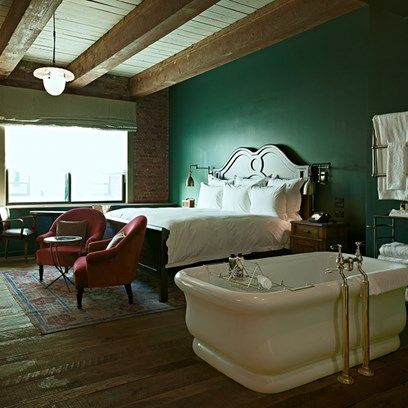 Dark Green Bedroom with Rolltop Bath in Bedroom Ideas. This large bedroom in Soho House New York has exposed beams and light fitting for an industrial feel without compromising on comfort.