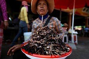 Kampong Cham, Cambodia. A woman sells fried tarantulas at a market