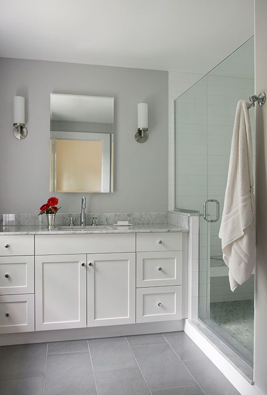 white painted full overlay shaker style custom bath vanity with marble top porcelain tile floor grey walls and frameless shower door