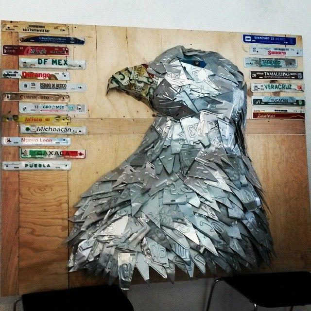 Es una escultura de una águila construida con placas automotrices recicladas