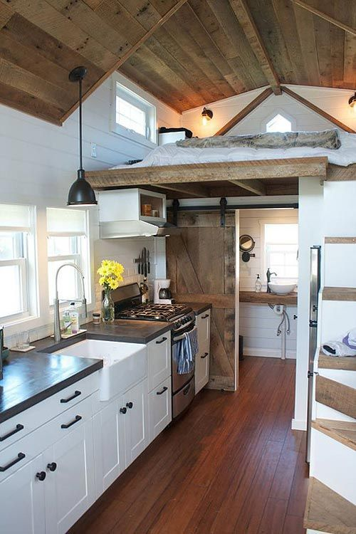 Tiny house with a custom concrete countertop, farm sink, freestanding range, and refrigerator under the storage stairs.