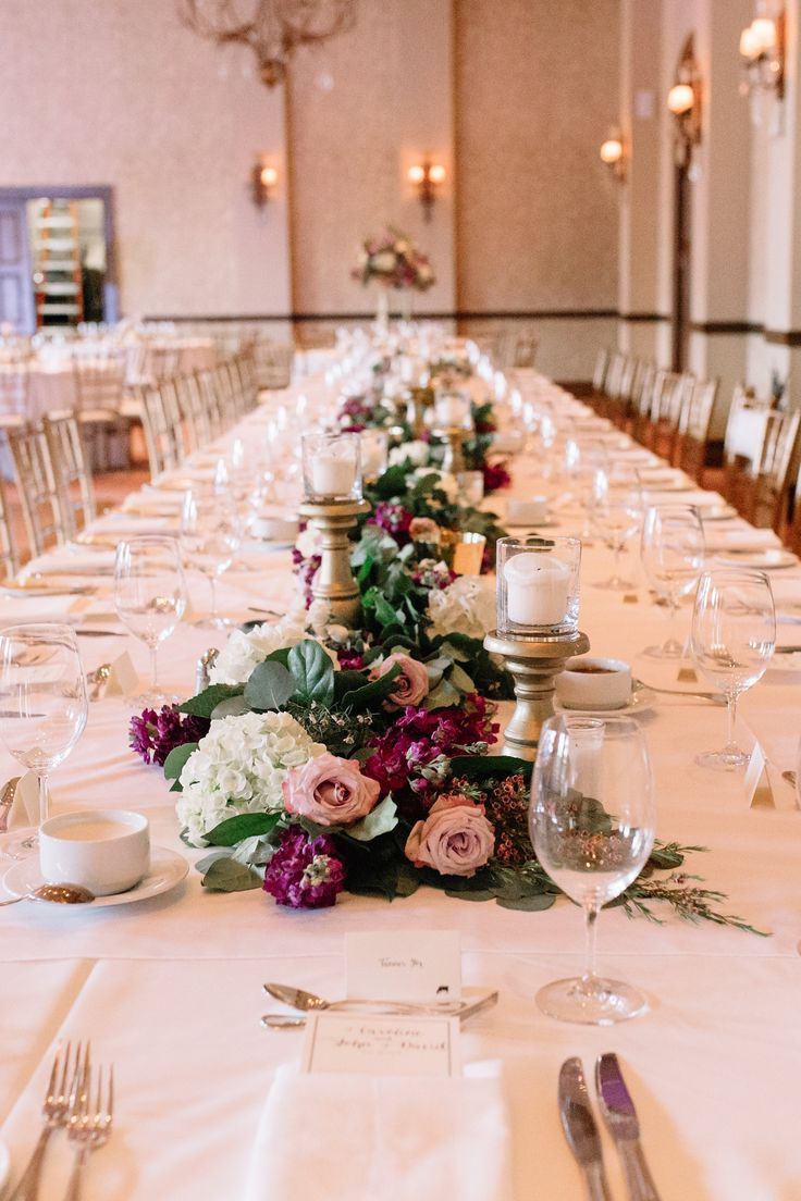 wedding reception head table is made grand by a full and lush garland of eucalyptus and lemon leaf, filled with white hydrangea, purple stock, lavender roses, and light pink wax flower. pillar candles on gold pedestals are peppered down the length of the garland.
