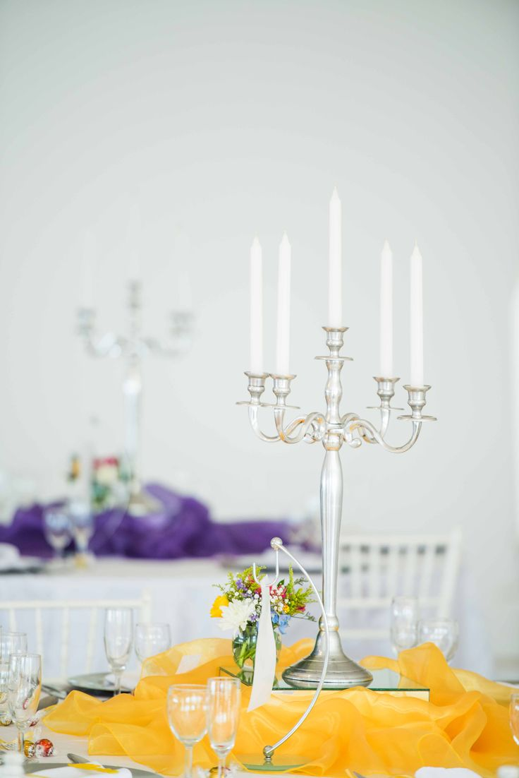 Monte Vista Venue rainbow centerpiece with a white candles on a silver candelabra and a small glass bowl with a mix of flowers in, all on a mirror box surrounded by yellow organza with a table number hanging from a steel and glass stand.