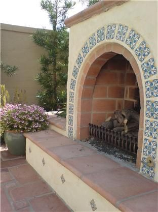 The hand-painted tile decorating this arched outdoor fireplace adds just the right touch to this Spanish-inspired landscape. Design by Studio H Landscape Architecture in Newport Beach, CA.