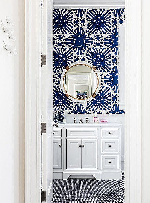 Bold blue and white bathroom with coordinating colors of penny tiles and patterned wallpaper.