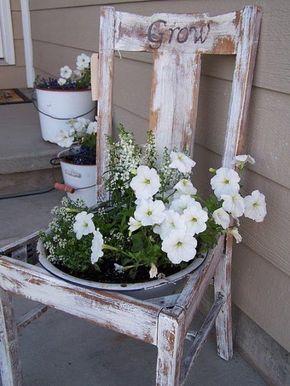 une vieille chaise en bois blanc transformée en pot de fleurs