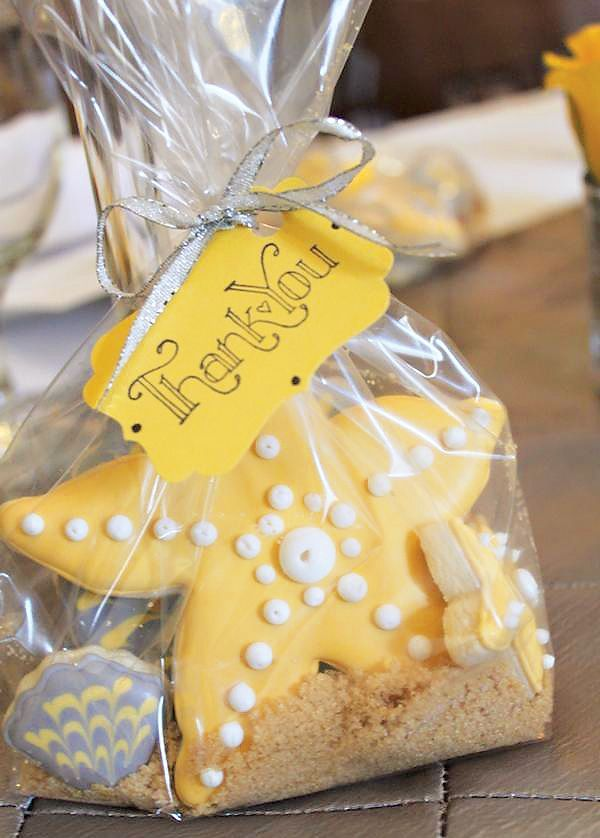 A Beachy Bridal Shower with heart shaped silver seashell backdrop, yellow & gray starfish & seashell desserts, 'LOVE' topped cupcakes + lace & pearl sugar high heel cake topper