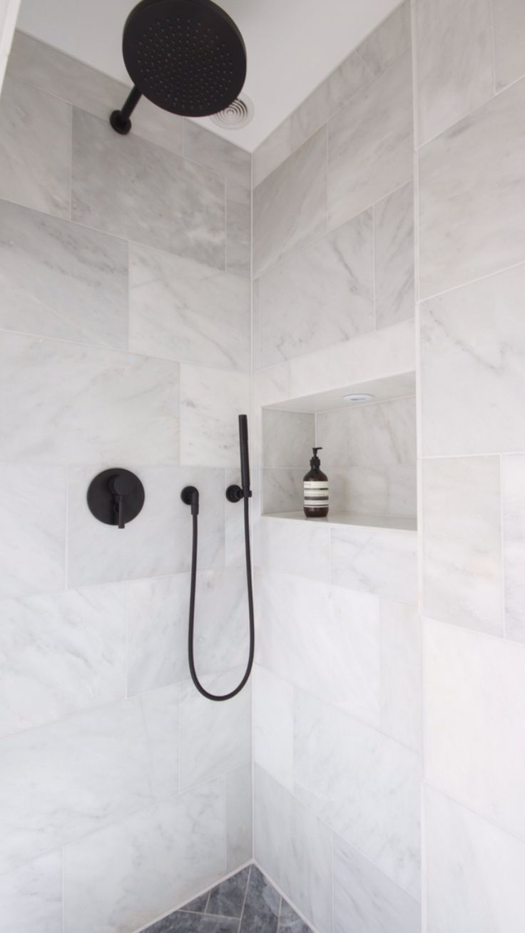 White Marble shower with black Dornbracht tapware and herringbone marble flooring.