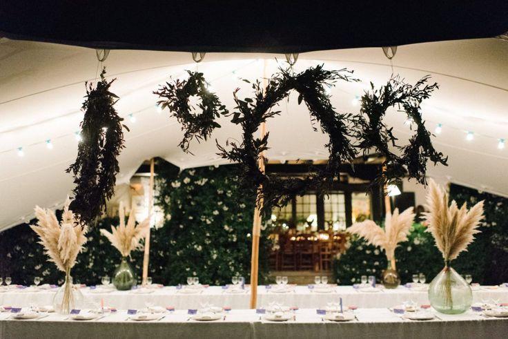 tente berbère, grande couronne de végétation, assiettes en céramique blanche, grande dame jeanne avec plumeaux, serviettes brodée personnalisée , chemin lumineux en bougies