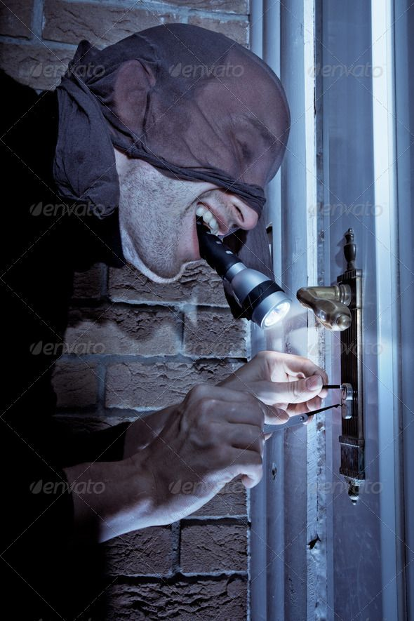 Masked burglar holding a flashlight in his mouth, picking the lock of a door. http://photodune.net/item/burglar-picking-door-lock/2733450