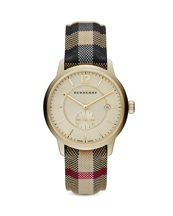 A mix of polished patterns-from the jacquard check strap to the subtle twill-like dial-makes Burberry's oversized timepiece a new classic.   Gold tone–plated stainless steel/cotton/nylon/leather   Mad