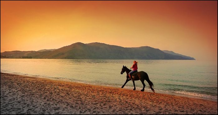 Georgoupolis, Crete island, Chania: On the beach a woman is riding a horse into the sunset.