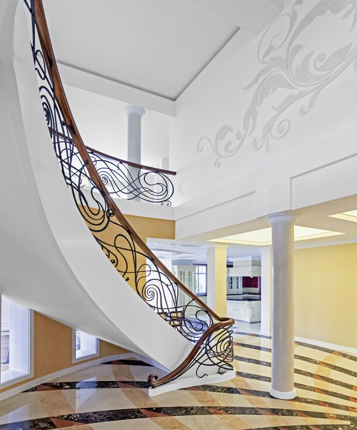 ST490 Double-sided curved stringer stair mounted on a concrete substructure. Stringers of painted oak, a hand-wrought steel balustrade with a wooden handrail. Stone treads. Private residential project , designed by TRĄBCZYŃSKI.