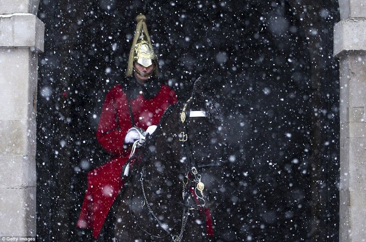 member of the Household Cavalry is seen on guard at Horse Guard's Parade as snow falls in ...