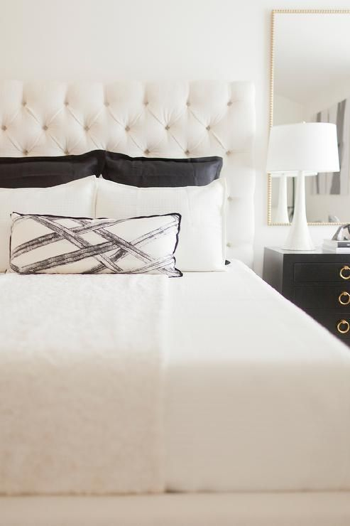 Black And White Bedroom Features A White Tufted Bed