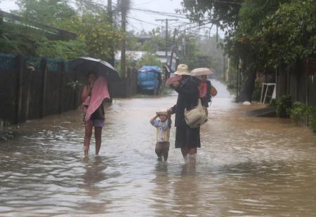 7日、フィリピンのルソン島で、台風22号による大雨で冠水した道路を歩く家族(AP=共同) ▼8Dec2014共同通信|台風22号マニラ接近へ 勢力弱まるも警戒続く http://www.47news.jp/CN/201412/CN2014120801001227.html