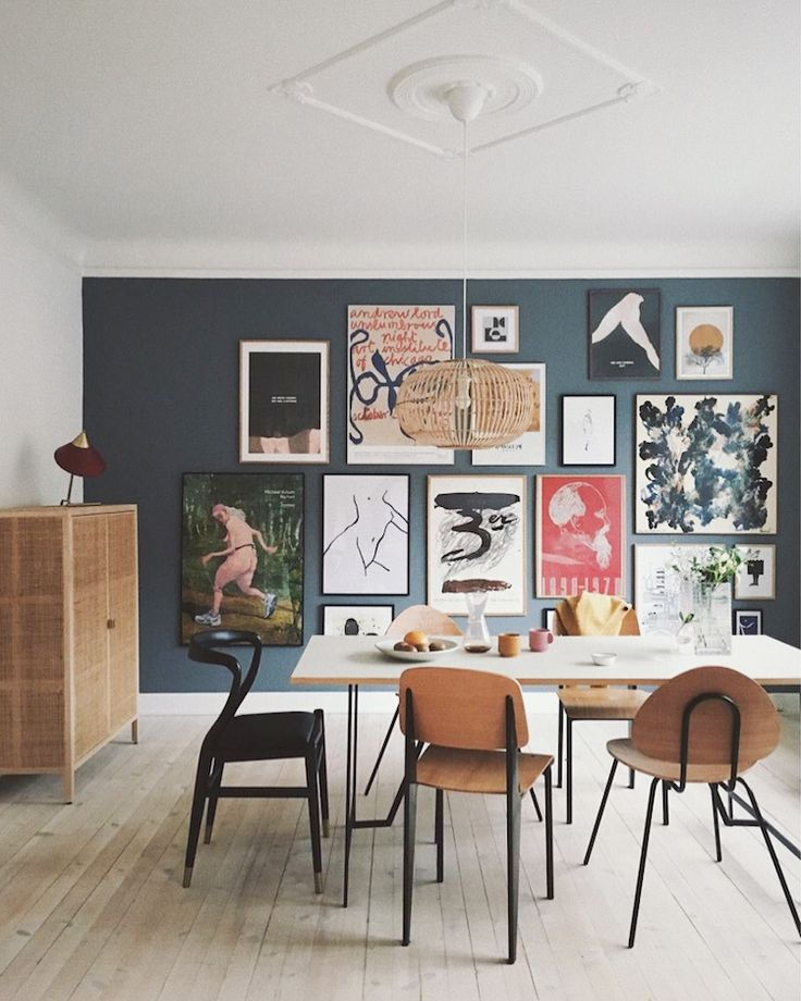Dining room with dark blue gallery wall in An Artf…