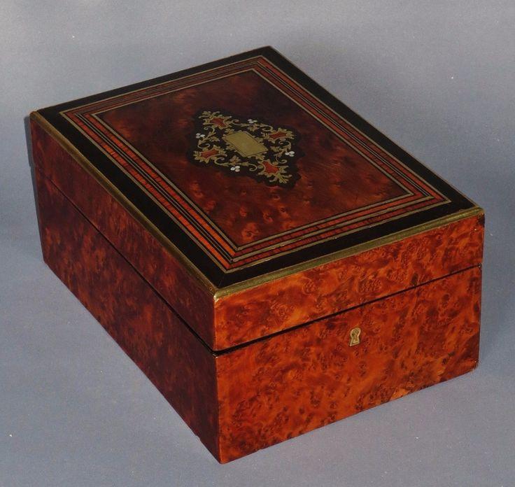 Наполеон III период шкатулка в тую с использованием темного дерева и латуни топ с центральным украшением в латунь, черное дерево, розовое дерево и перламутр. Красная атласная подкладка. Внутреннее зеркало. Хорошее Оригинальное состояние, но ключ отсутствует.  Longueur : 21,7 см Largeur : 15,5 см Вальяжностью : 10 см Эпоха : 19 век  Цена 390 €