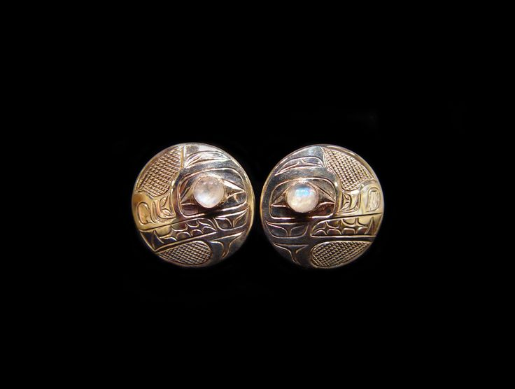 """Wolf Earrings, by Kwakwaka'wakw artists Chris Cook and GitksanTsimshian wife and designer Jessica Cook. Sterling silver, moon stone, measuring 0.75"""". Northwest Coast First Nations Jewelry."""