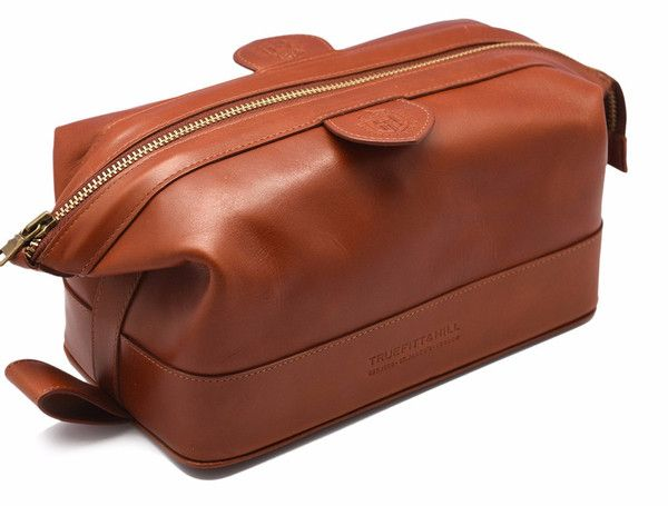 """Gentleman's Wash Bag. Also known as """"The Expandable Wash-bag"""" this compact leather case measuring 232mm by 105mm is the ideal travel container for your grooming supplies and accessories. Embossed with the Truefitt and Hill stamp on the flap. it's available in two traditional colours."""