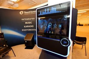 TouchTunes Interactive Networks Virtuo machine serves three functions: its a digital jukebox, a karaoke machine, and a photo booth that prints out strips of images with a variety of backgrounds. The machine can be rented for meetings and events.
