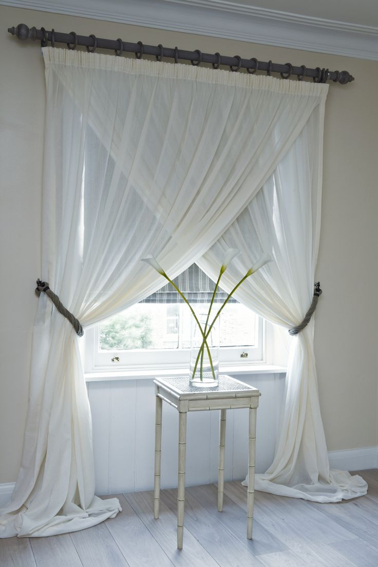 Cross over Voile Curtains with a fixed pencil pleat heading on a wooden pole held back with tie backs - with a striped roman blind