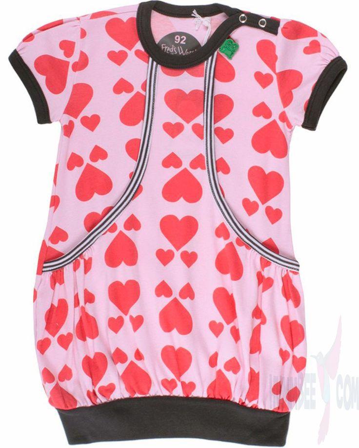 Lichtroze jurkje met korte mouwen in een jersey. Allover rood hartjesmotief. Drukknopsluiting op de linkerschouder.