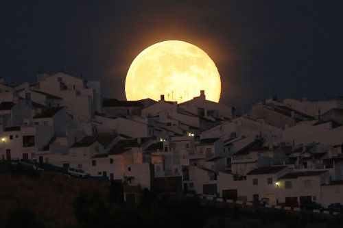 The Supermoon rises over houses in Olvera, in the southern Spanish province of Cadiz, July 12, 2014.
