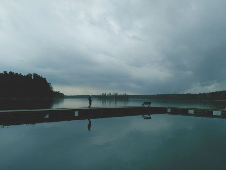 There's an amazing and quiet place where we spent a few days relaxing our minds... My love as a model of lone man walking by the lake. Nidzkie Lake in Ruciane Nida, Masuria Lakes in Poland, Europe. Gloomy mood and nostalgia colors.