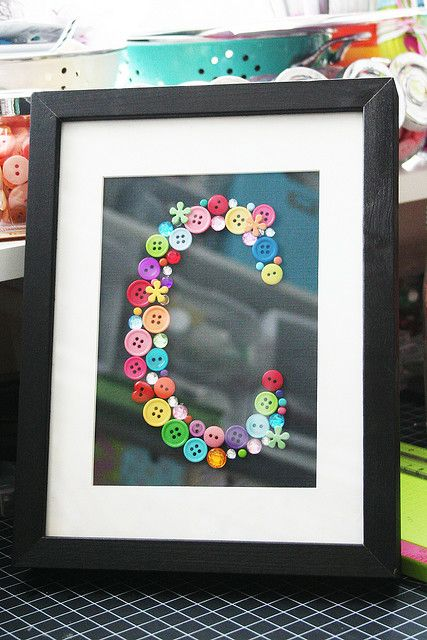 Print a letter from a printer, and glue on various vintage buttons. Love the black background and framing. - cute for a kids room!