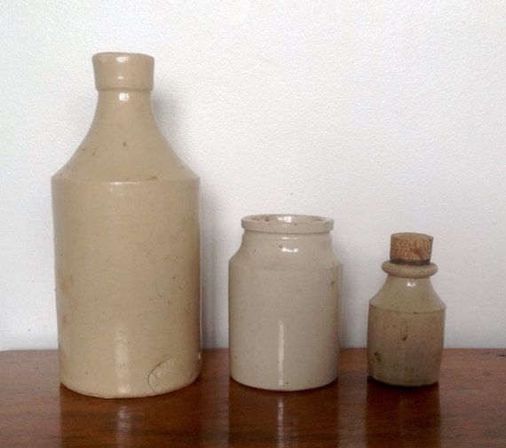 A trio of pale stoneware pots from the early 1900s.  1. Tall bottle...7 tall by 2.3 diameter, has a partial stamp at base. No chips or cracks. 2. Small jar...3.3 tall by 2.2 diameter at base, 1.6 across neck, no chips or cracks. 3. Small bottle with cork...2.4 tall ( exc. cork) 1.2 diameter, also in good condition.  All three pots have darker marks and rough bits of glaze which adds to their character...please see photos .  Please note: We are happy to post our vintage items anywhere in the…