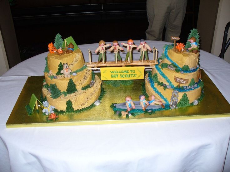 I made this for my son's Blue & Gold banquet (cub scouts).  For those who aren't familiar with it, that is when the boys who have reached the highest level of cub scouts bridge over to boy scouts.  The cake on the left is the cub scout mountain (each animal represents a cub scout rank: bobcat, tiger, wolf, bear).  The mountain on the right is the boy scouts mountain.  The boys crossing the bridge are fondant representions of the boys who were bridging this year.  All BC with ...
