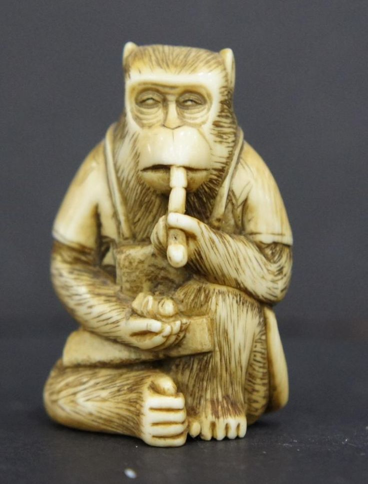 JAPANESE IVORY MONKEY NETSUKE. MONKEY HOLDING FLUTE, SIGNED Prospective purchasers are advised that several countries and some states prohibit the importation of property containing materials from endangered species, including but not limited to coral, ivory and tortoiseshell. Accordingly, prospective purchasers should familiarize themselves with relevant customs regulations prior to bidding if they intend to import this lot into another country or state.