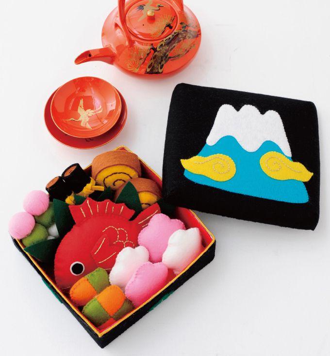 おいしそうなおせち料理の豪華なお飾りです。 重箱のふたには富士山のアップリケをして、お正月に一層おめでたい雰囲気に。 重箱の中には、鯛、梅の紅白かまぼこ、練り物、 三色だんご、昆布巻き、伊達巻が入っています♪