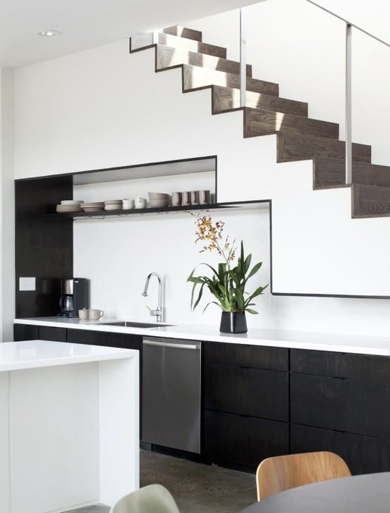 Black and White Kitchen; sink area recessed under stairs