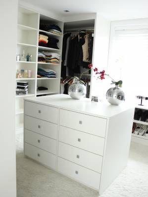 Inloopkast gemaakt van wit melamine. Rondom de kamer zijn kasten ingebouwd, hierbij is rekening gehouden met ieder kledingstuk.