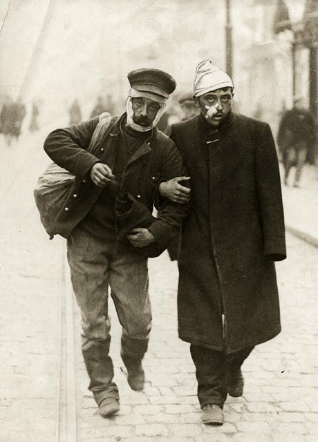 A wounded German and wounded Belgian walk arm in arm, 1915.