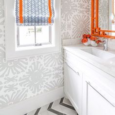 Grey and orange bathroom features walls clad in gray print wallpaper, Quadrille Sigourney Wallpaper, lined with a white washstand and white countertop under an orange bamboo mirror next to a window dressed in a blue trellis roman shade accented with orange trim alongside a gray chevron tiled floor.