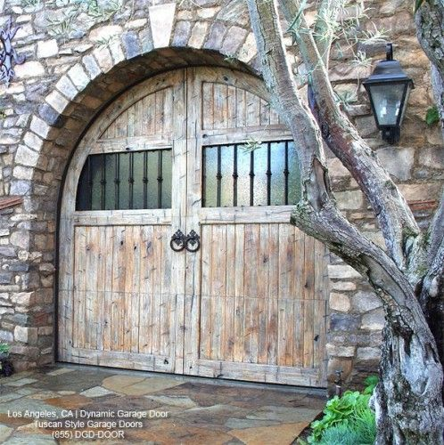 Another gorgeous distressed wood garage door with textured, frosted glass. The stone is beautiful as well.