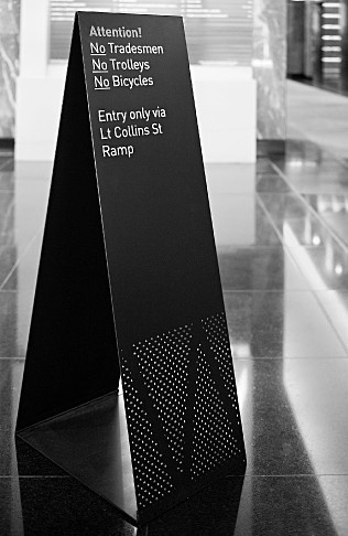 Sandwich Board for 114 William Street by Hofstede Design. An identity for internal and external signs as part of the revitalisation of this prominent William street site.     Providing a more defined presence for the building at street level, the main location sign is a three metre high lightbox wrapped with perforated anodised aluminium panels.