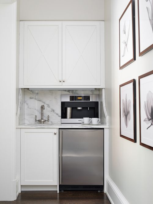Kitchen with built-in coffee station boasting crisp white cabinets fitted with a stainless steel mini fridge paired with white marble countertop and backsplash lined with an integrated coffee maker next to a round sink and stain nickel faucet.