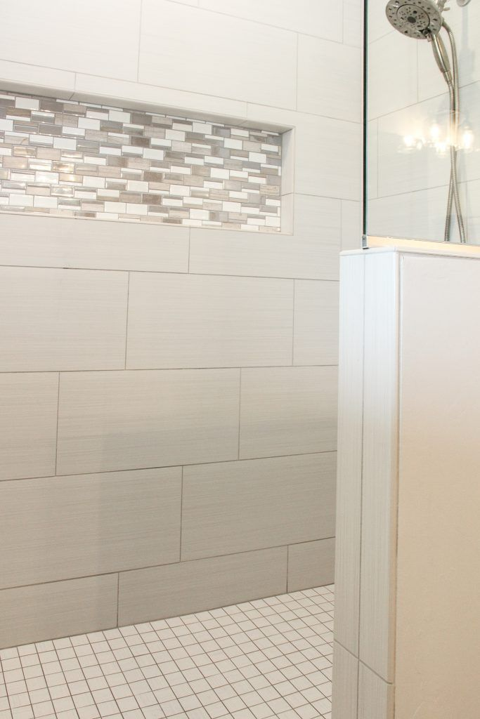 White Tiled Shower With Blue Glass Tile Accent Strip And Niche