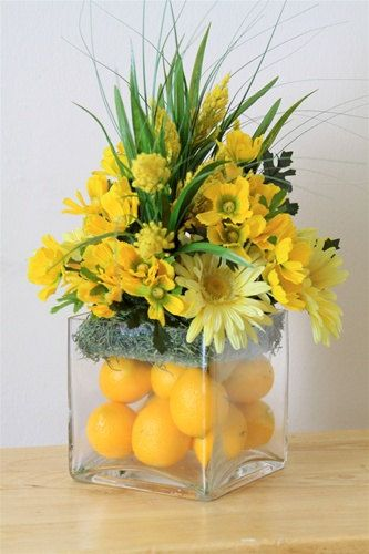 Yellow centerpiece w/daisies [like lemons in square glass vase. not sure about flowers on top]