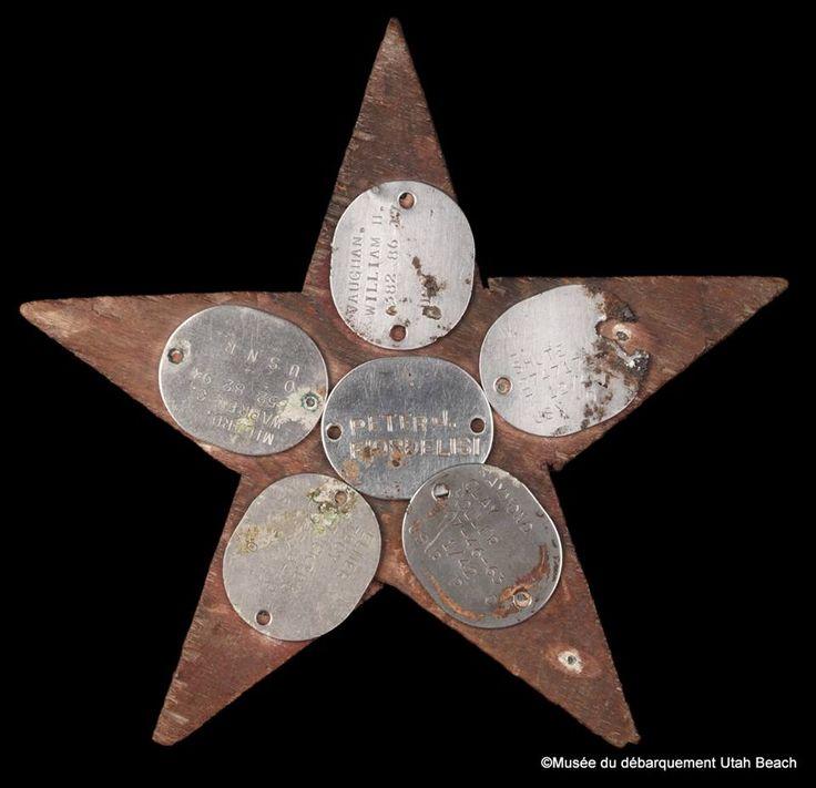 Embarqués sur l'USS Corry, Peter Fiordelisi, Warren Milard, William Shute, Elmer Stockton et William Vaugham, (cinq marins) nouèrent de profonds liens d'amitiés. Ils survécurent aux événements dramatiques de ce 6 juin 1944. A la fin de la guerre, ils fabriquèrent cette étoile à cinq branches en bois pour y fixer leurs plaques d'identité. Au cours des années 1970, l'un de ces anciens marins,donna au musée cet objet qui cristallisait pour eux cette page tragique de l'histoire.