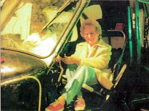 Mrs. Sayer and some friends were visiting the Fleet Air Arm Station at Yelverton, Somerset, England in 1987 when this photo was taken. They thought it would be cute to take a picture of her sitting in the seat of retired helicopter. Mrs. Sayer insists no one was sitting next to her in the pilot's seat... although a figure in a white shirt can clearly be seen sitting there.