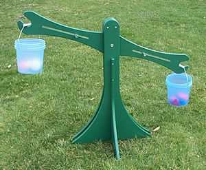 The Balance Scale is a portable, outdoor scale for your natural preschool playground. It is a wonderful piece of outdoor learning equipment for teaching about math and science concepts. Children can place a manipulative or loose part into each bucket and observe as one side lowers and one side raises, showing them which object weighs more and which object weighs less. Children can also put sets of items into each bucket to compare the weights of several items placed together.