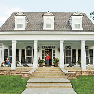 Love the front porch, but a little landscaping would soften it. Plant some monkey grass people! A shrub? A bush?... But I do love the porch, white house, black shutters, dormers...