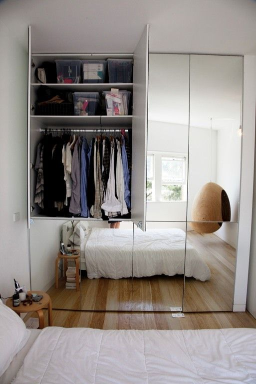 Mirror fronted wardrobe in a simple bedroom. Photo by Todd Selby